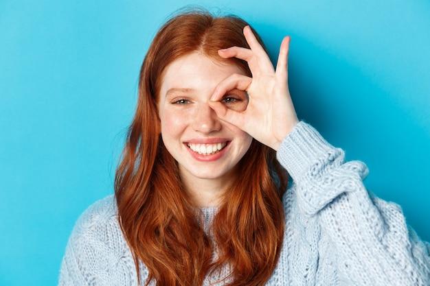 Tiro na cabeça do modelo feminino ruiva alegre mostrando sinal bem sobre o olho, sorrindo satisfeito e feliz, em pé contra um fundo azul.