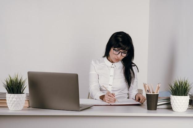 Tiro na cabeça freelancer agradável jovem feliz trabalhando no computador em casa. mulher de negócios atraente estudando online, usando o software do laptop, informações de navegação na web ou compras na loja da internet.