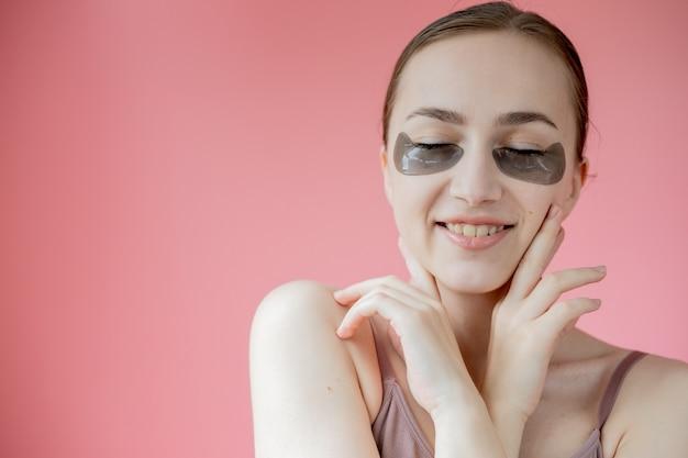 Tiro na cabeça retrato close-up sorridente jovem com máscara de adesivos hidratantes sob os olhos olhando