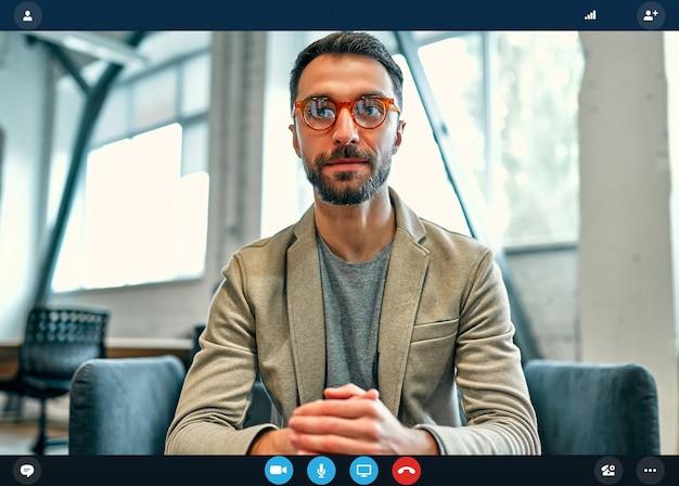 Tiro na cabeça, retrato da aplicação da tela do trabalhador caucasiano em entrevista online usando webconferência no computador, jovem empresário falando por videochamada no laptop com um parceiro de casa