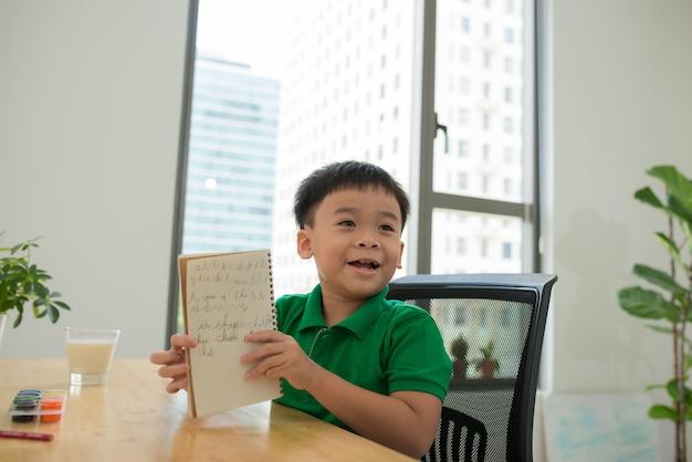 Tiro na cabeça retrato de criança bonita asiática feliz fazendo lição de casa com o rosto sorridente em casa.