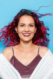 Tiro na cabeça retrato de uma garota de cabelo ruivo ruivo feliz com sardas, sorrindo, olhando para a câmera. fundo azul pastel. copie o espaço.