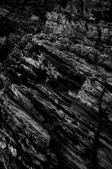 Tiro na escala de cinza vertical dos padrões nas falésias rochosas