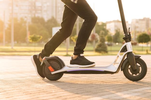 Tiro nas pernas jovem de tênis preto passeio de scooter móvel elétrica. close-up pés homem correio entrega de comida anda na rua em scooter elétrico entregar pedido de cliente on-line ao pôr do sol