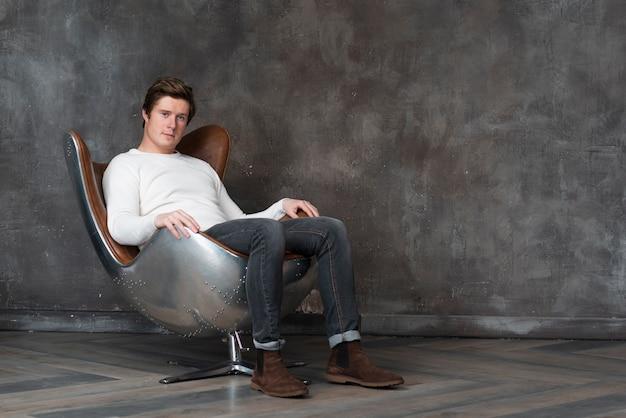 Tiro no escuro jovem sentado na poltrona de couro