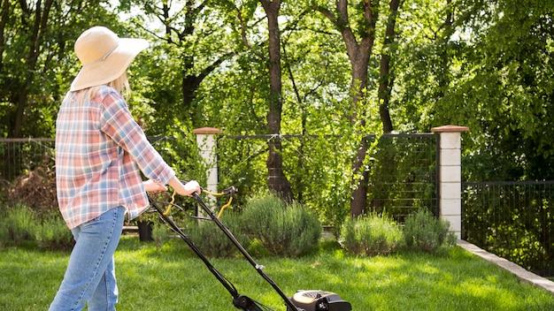 Tiro no escuro mulher cortando a grama