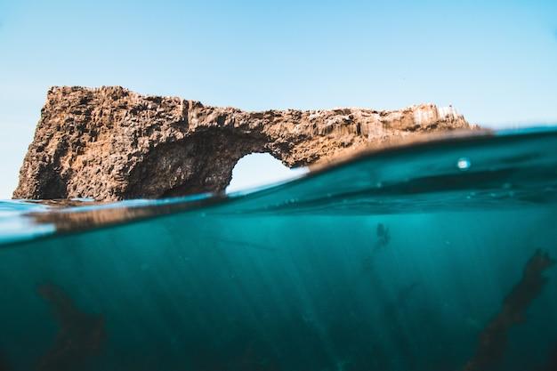 Tiro no nível da superfície da água de rochas e recifes no mar em um dia ensolarado