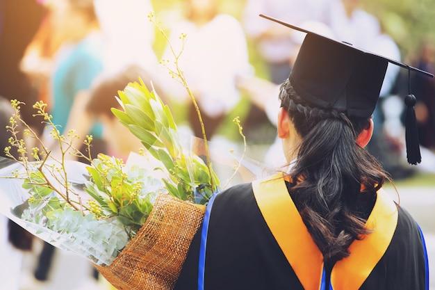 Tiro o verso da jovem aluna na mão segurando um buquê de flores durante a formatura na universidade.