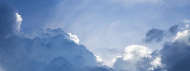 Tiro panorâmico do céu azul nublado com raio do sol atrás da nuvem branca, conceito esperançoso.