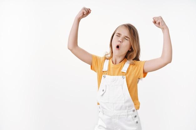 Tiro para cima feliz, triunfando jovem feliz garotinha conquista sucesso, ganhando comptetion, fazer pose vencedora, celebrando o punho fechado, puxando a cara, feche os olhos alegres, fique de pé na parede branca