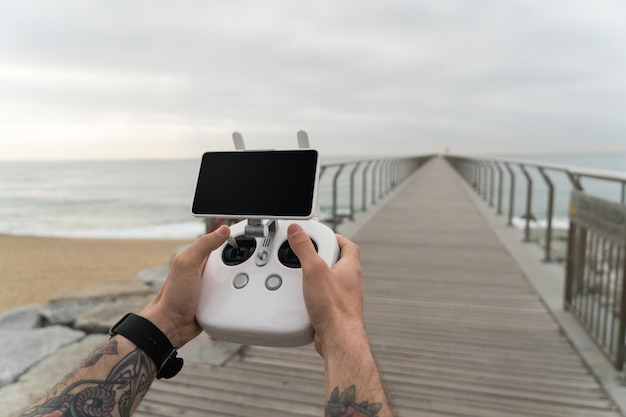 Tiro pov do usuário moderno e milenar da nova geração de novas tecnologias futuristas, use o controle remoto do drone para voar o dispositivo no ar.