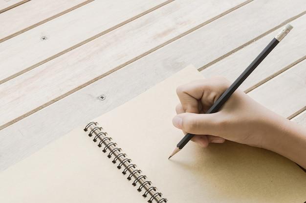 Tiro próximo de uma mão humana escrevendo algo no papel, foco seletivo na mão