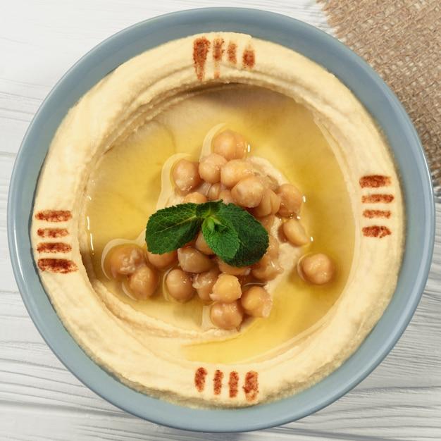 Tiro quadrado da vista superior do prato de hummus na mesa de madeira