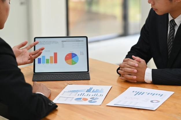Tiro recortado consulta com tablet digital e planejamento de marketing.