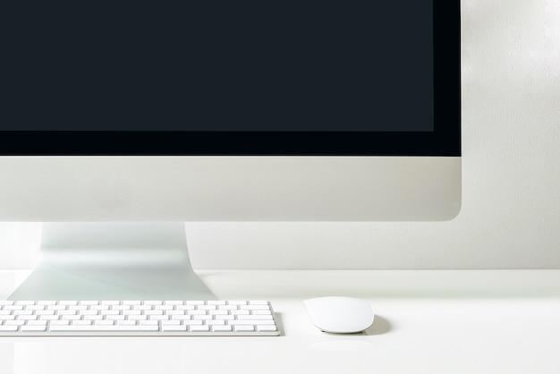Tiro recortado de computador desktop na mesa branca com espaço de cópia