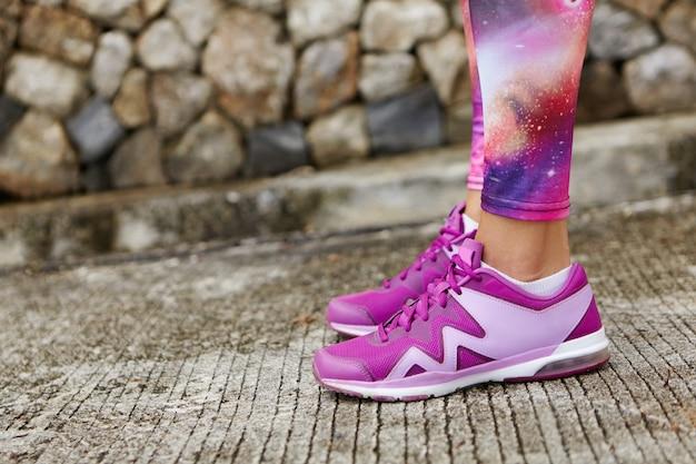 Tiro recortado de corredor de mulher apto usando tênis violeta e legging de impressão espacial em pé sobre o concreto de pedra enquanto se prepara para o treino de corrida.