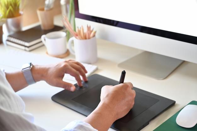 Tiro recortado de designer trabalhando com tablet de desenho digital de desenho para design criativo no escritório