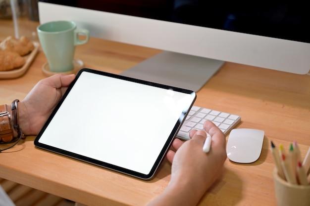 Tiro recortado do empresário sentado e woking com tablet no escritório