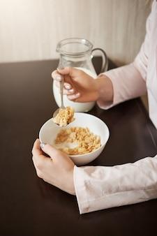 Tiro recortado vertical de mulher sentada na cozinha, segurando a colher enquanto come uma tigela de cereais com leite, tomando café da manhã saudável e aproveitando a bela manhã com a família, discutindo planos para hoje