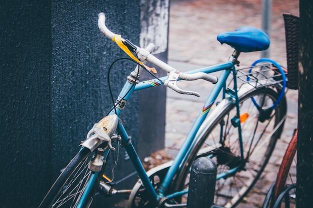 Tiro seletivo closeup de uma bicicleta azul estacionada perto de uma parede