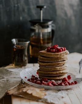 Tiro seletivo closeup de uma pilha de panquecas com frutas vermelhas em um prato perto de uma jarra de chá