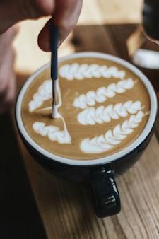 Tiro seletivo do close up do café com arte do café com leite em um copo cerâmico preto em uma superfície de madeira