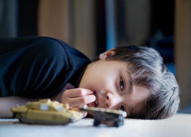 Tiro sincero criança feliz deitada no chão brincando com um brinquedo de carro de plástico