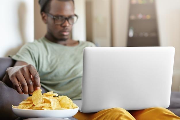 Tiro sincero de sério único macho concentrado de chapéu e óculos relaxantes em seu apartamento com computador portátil e prato de batatas fritas, rede de surf ou assistir série. foco seletivo na mão do homem