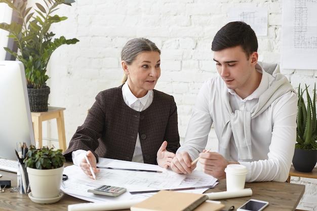 Tiro sincero do arquiteto feminino bonito maduro e seu jovem colega do sexo masculino discutindo na mesa do escritório, estudando esboços, desenhos ou plantas. arquitetura, engenharia e design