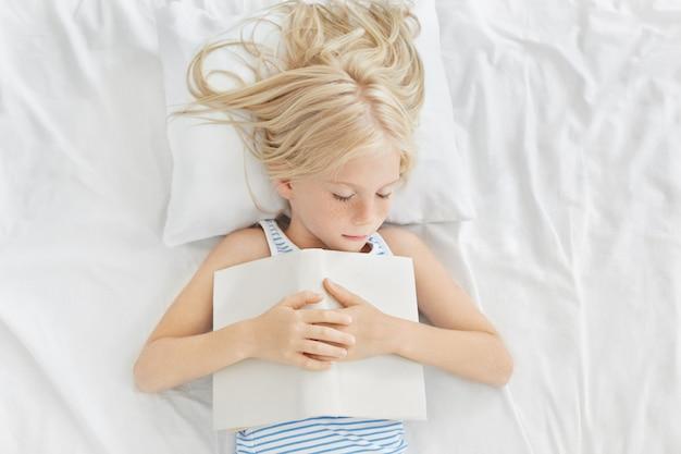 Tiro superior da criança fêmea pequena adorável que napping na cama. menina bonito com sardas e cabelos loiros, tendo um sono tranquilo com o livro aberto depois de ler uma história interessante, vendo bons sonhos