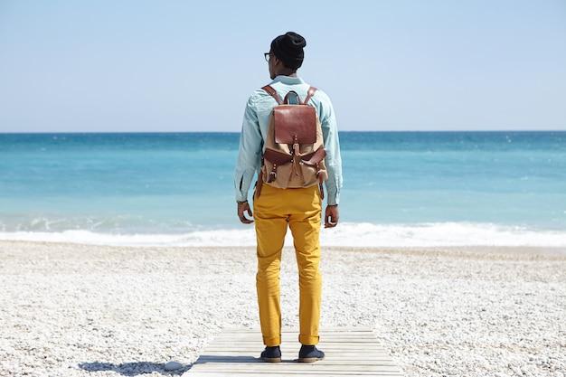 Tiro traseiro do elegante jovem mochileiro afro-americano em pé no calçadão na praia de calhau, de frente para o vasto oceano calmo com água azul clara durante a manhã pacífica, admirando a maravilhosa vista marinha