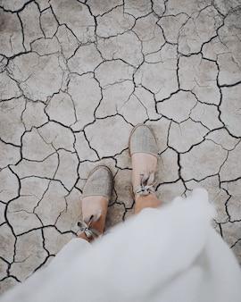 Tiro vertical aéreo dos pés de uma mulher em um chão rachado