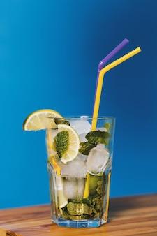 Tiro vertical closeup de coquetel de limão em um copo com dois canudos