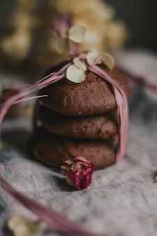 Tiro vertical closeup seletivo de biscoitos de chocolate empilhados, embrulhado com um fio rosa