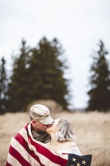 Tiro vertical com foco raso de um soldado americano beijando sua amada esposa