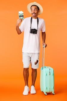 Tiro vertical completo animado feliz viajante masculino afro-americano, mal posso esperar para saborear um coquetel sob o sol e curtir férias incríveis, segurando bagagem, mala e passaporte com bilhetes