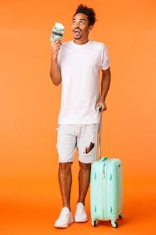 Tiro vertical completo cara afro-americana sonhadora e animada de férias, segurando bagagem, carregar mala e passaporte com bilhetes de avião, viagem perfeita de imagem, viagem incrível, laranja