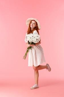 Tiro vertical completo feliz e alegre mulher atraente, com cabelos longos vermelhos, chapéu de palha, vestido de verão branco bonito, dançando, voltando para casa a partir de um encontro romântico com flores, segurando o buquê