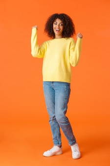 Tiro vertical completo sortudo e emotivo, garota bonita afro-americana, sentindo-se como vencedor, punho e sorrindo satisfeito, obteve aprovação, alcançou objetivo, ganhou o prêmio