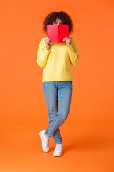 Tiro vertical completo tímida e bonita garota urbana moderna afro-americana com corte de cabelo afro, rosto escondido atrás de caderno vermelho e câmera espreita, escrevendo no diário, em pé laranja