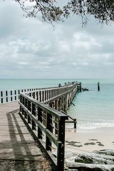 Tiro vertical da bela vista do oceano com um cais de madeira na costa