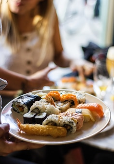 Tiro vertical da mão de uma pessoa segurando um prato de sushis