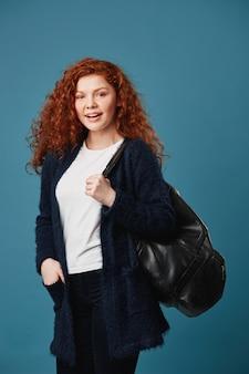 Tiro vertical da mulher bonita jovem estudante de cabelos vermelhos com penteado ondulado, segurando a mão no bolso, sorrindo brilhantemente, posando com mochila.