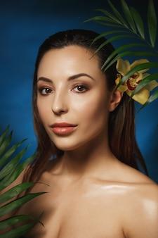 Tiro vertical da mulher bonita sorridente com flor no cabelo.