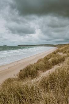 Tiro vertical da praia coberta de grama pelo oceano calmo capturado em cornwall, inglaterra