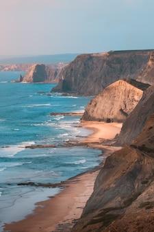 Tiro vertical das belas falésias rochosas à beira-mar sob o incrível céu azul claro