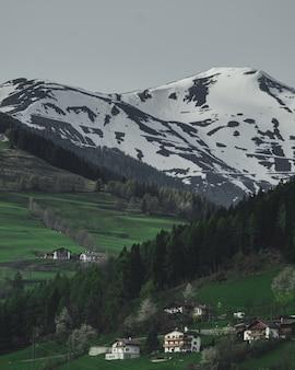 Tiro vertical das casas em uma colina com a bela montanha coberta de neve