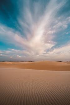 Tiro vertical das colinas de areia sob as belas nuvens no céu