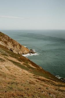 Tiro vertical das colinas pelo corpo de água sob um céu claro