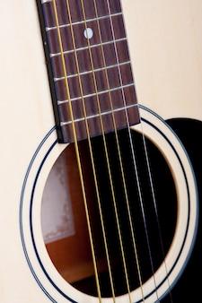 Tiro vertical das cordas de uma guitarra branca durante o dia
